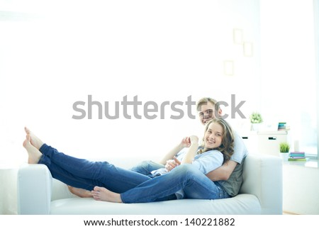 Young man and his girlfriend lying on sofa and looking at camera - stock photo