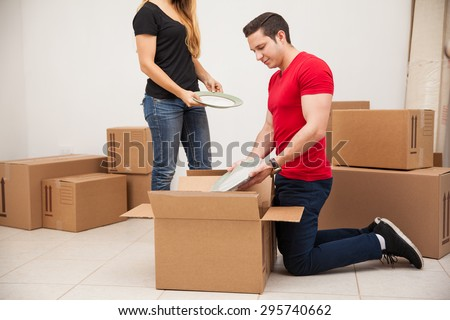 Young man and his girlfriend putting some of their stuff in boxes before moving out to their new place - stock photo