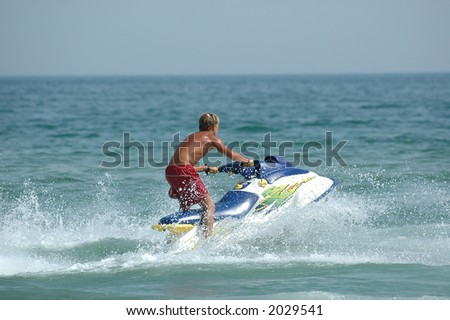 Young man and his jet-ski - stock photo