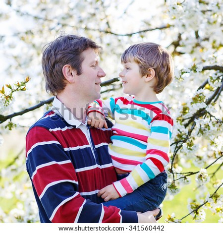 Young man and his little son in blooming cherry garden in spring. Happy family celebrating father's day. - stock photo