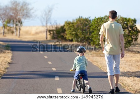 young man and his son at the balance bike walking and exercising - stock photo