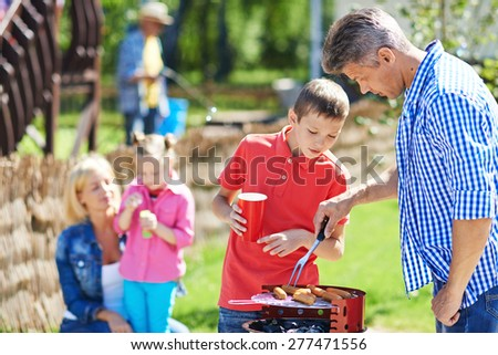 Young man and his son frying sausages on grill outdoors