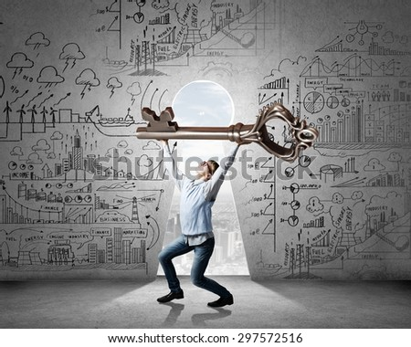 Young man and keyhole at background lifting big key above head - stock photo