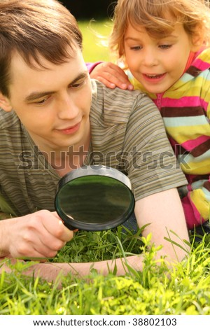young man and little girl look through magnifier - stock photo
