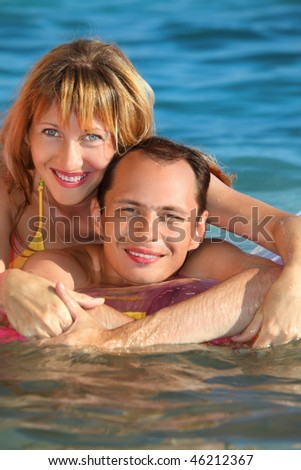 young man and nice women lying on an inflatable mattress in pool, woman lying astride man - stock photo