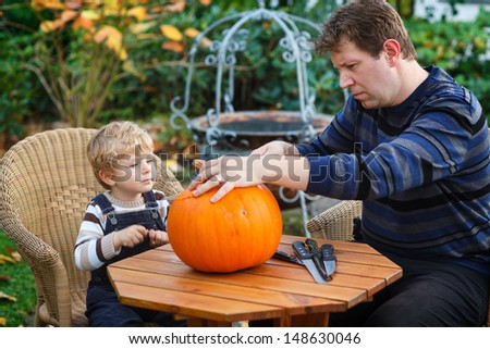 Young man and toddler boy making jack-o-lantern for halloween in autumn garden - stock photo