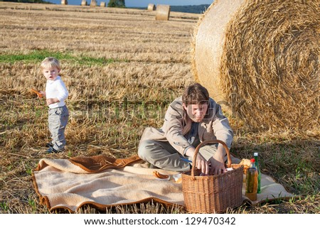 Young man and two little toddler boys making evening picnic on hay field, Germany.