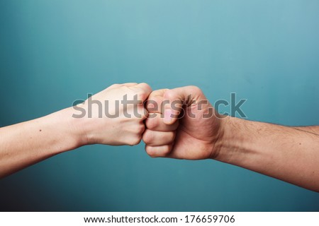 Young man and woman are fist bumping - stock photo
