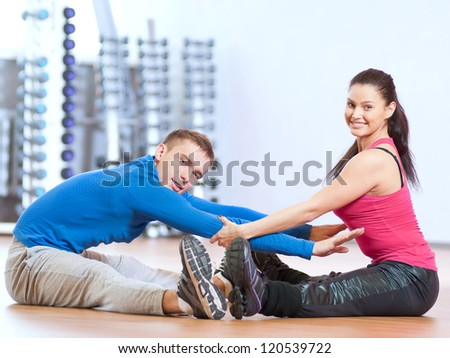 Young man and woman at the fitness gym is doing stretching exercises