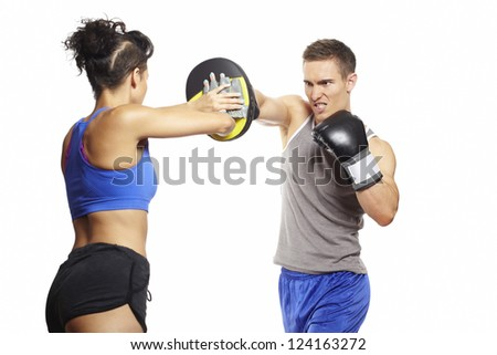 Young man and woman boxing sparring in sports outfits on white background - stock photo