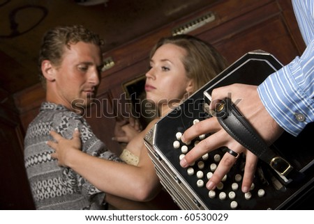 Young man and woman dancing tango with passion - stock photo