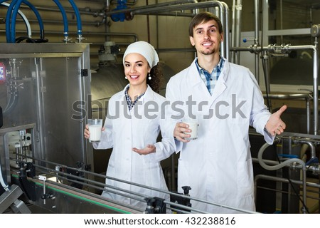 young man and woman dressed in lab coats working on the dairy factory