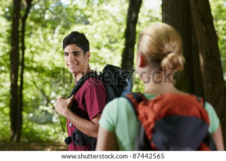 young man and woman during hiking excursion, with man looking over shoulders. Horizontal shape, rear view, waist up - stock photo