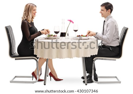 Young man and woman eating on a date seated at a restaurant table isolated on white background - stock photo
