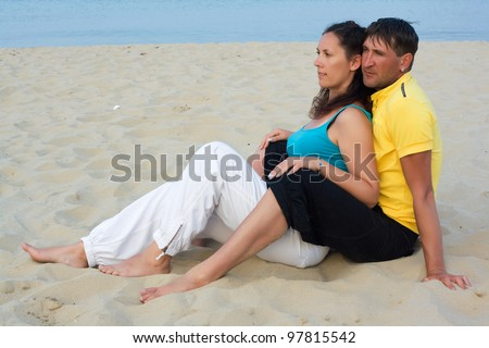 young man and woman embracing as a romantic couple standing in the sea on a beach with a blue