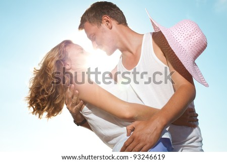 Young man and woman embracing under  the bright sun - stock photo