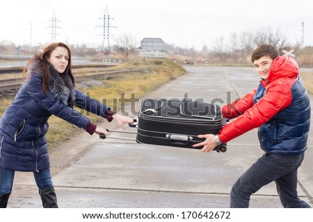 Young man and woman fighting and arguing each pulling on one end of a suitcase as they stand in a rural road alongside a railway line - stock photo