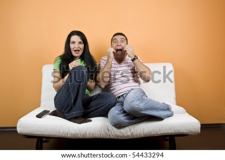 Young man and woman ,friends watching TV  a horror movie and they are scared - stock photo