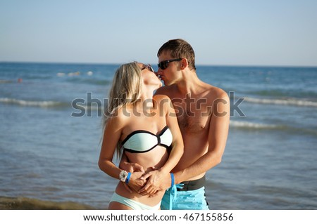 Young man and woman have a rest at the sea and kissing