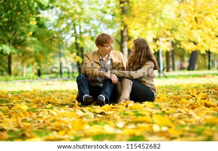 Young man and woman in a park by fall - stock photo