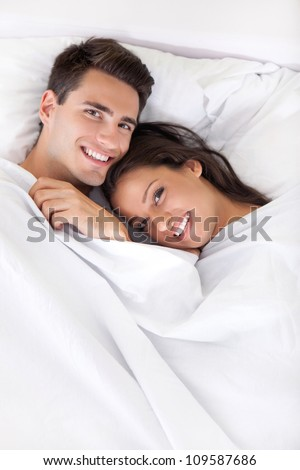Young man and woman in bed. Couple. - stock photo