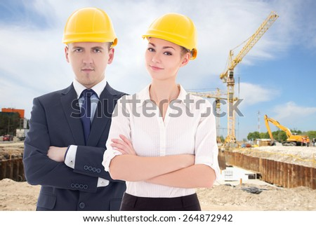 young man and woman in builder 's helmets at construction site - stock photo