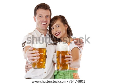 Young man and woman in dirndl holding oktoberfest beer stein. Isolated on white background. - stock photo