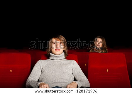 young man and woman in the cinema to enjoy the movie - stock photo