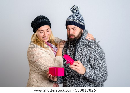 young man and woman in winter dress with gift box - stock photo
