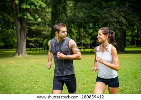 Young man and woman jogging outdoor and looking on each other - stock photo