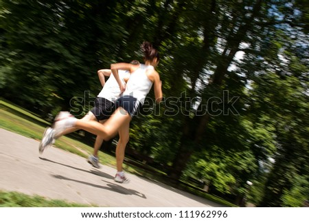 Young man and woman jogging outdoor in nature - motion blur image (panning) - stock photo