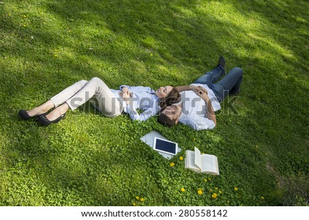 Young man and woman napping on grassy lawn. Cute young man and woman casual dress official shirt napping dreaming lie on green grass with yellow flowers laptop tablet PC book around - stock photo