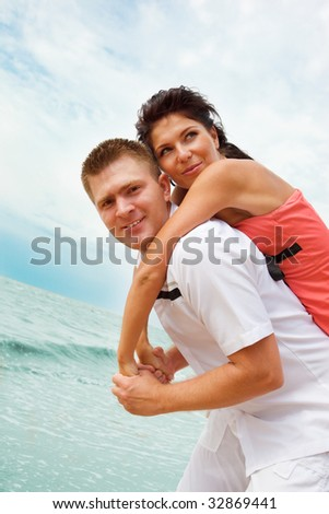 Young man and woman playing on the beach