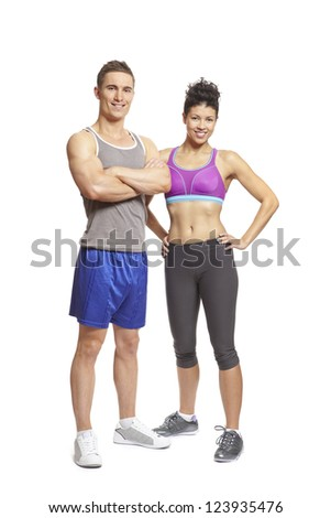 Young man and woman relaxing in sports outfits on white background smiling - stock photo