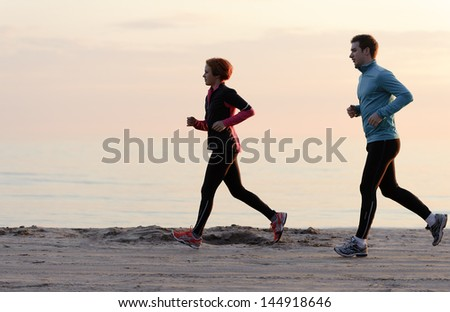 Young man and woman running along the waterfront