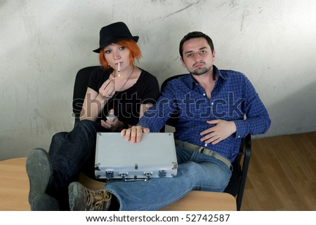 Young man and woman sitting on a vintage background