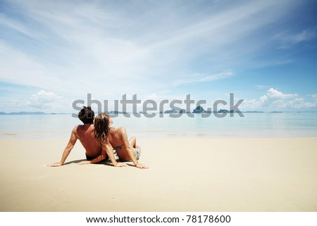 Young man and woman sitting on warm sand by a sea and looking to somewhere