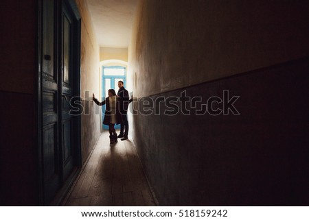 young man and woman standing in a dark corridor