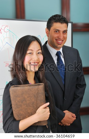 Young man and woman standing near whiteboard - stock photo
