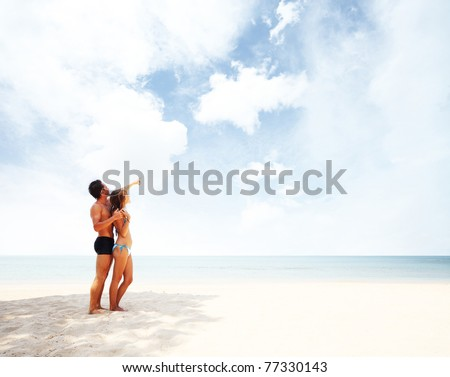 Young man and woman standing on warm sand at sunny day and enjoying each other - stock photo