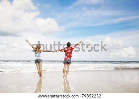 Young man and woman standing together on wet sand on cloudy sky background
