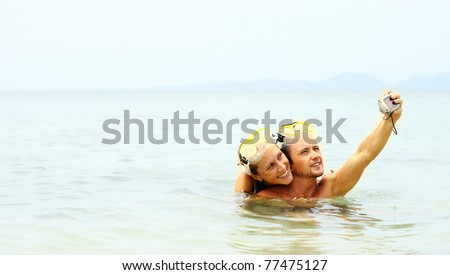 Young man and woman taking the picture of them self in the sea - stock photo