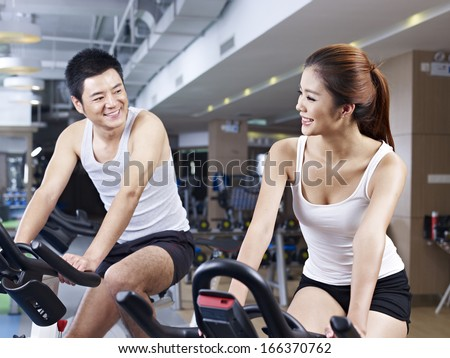 young man and woman talking while exercising on bicycle in fitness center.