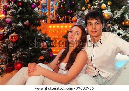 Young man and woman wearing white shirts sit near green trees in snow with Christmas balls - stock photo