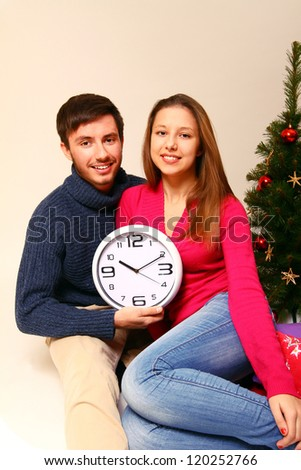 Young Man And Woman With A Clock And A Christmas Tree Isolated