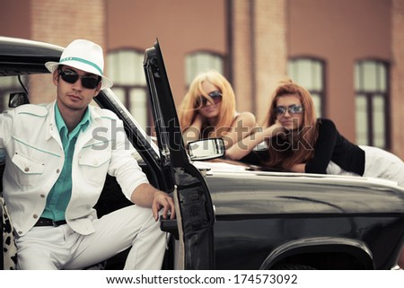 Young man and women at the retro car  - stock photo