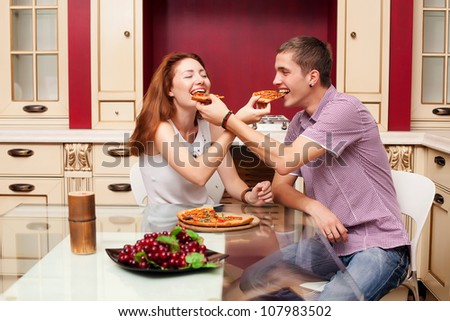 Young man and young woman feed pizza to each other - stock photo