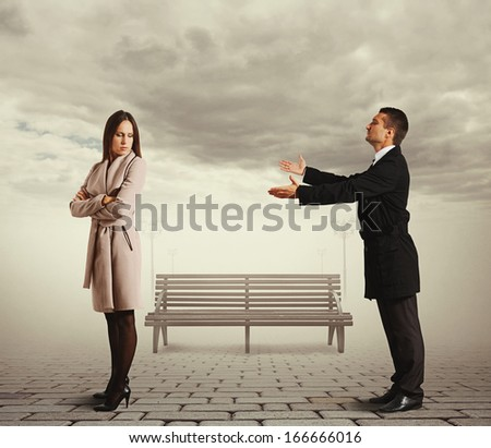 young man apologizing to woman at outdoor - stock photo