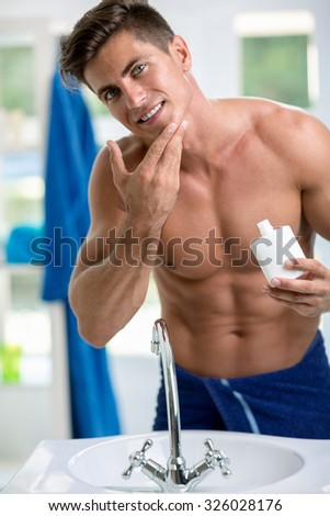 Young man applying after shave,  portrait of a young handsome man with a skin for shaving - stock photo