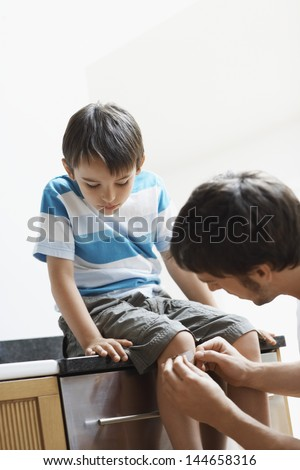 Young man applying bandage on his son's knee at home